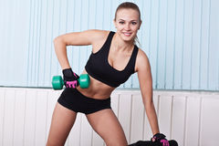Smiling sportswoman lifting dumbbells Royalty Free Stock Photography