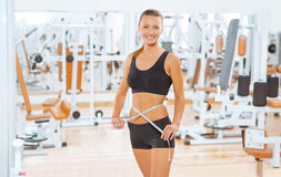 A smiling sportswoman with measure tape Stock Photos