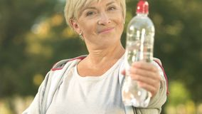 Smiling sportswoman showing bottle of water and thumbs up, health care, activity. Stock footage stock video