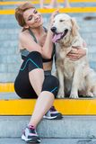 Sportswoman sitting with dog. Smiling sportswoman sitting with golden retriever dog on stairs in city stock images