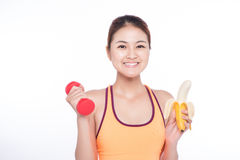 Smiling sporty asian  woman holding banana over white background. And looking at camera Royalty Free Stock Image