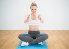 Smiling sporty blonde sitting cross legged on exercise mat showing thumbs up Stock Image