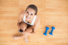 Smiling sporty brunette holding a mobile phone and sitting next to dumbbells Royalty Free Stock Images