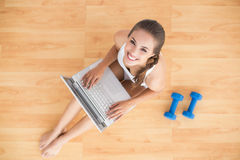 Smiling sporty brunette using a laptop and sitting next to dumbbells Stock Photos