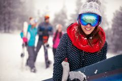 Smiling sporty female holds snowboard in mountains on winter. Holiday Royalty Free Stock Image