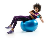Smiling sporty girl doing fitness exerrcise on gymnastic ball. Stock Image