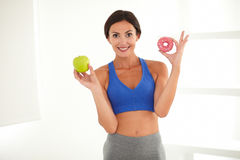 Smiling sporty lady on a diet deciding Royalty Free Stock Image