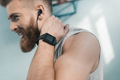 Smiling sporty man with smartwatch on wrist royalty free stock image