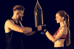 Smiling sporty man and woman standing with dumbbells on black royalty free stock images
