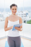 Smiling sporty model scrolling on tablet pc Stock Photography