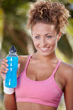 Smiling sporty woman with bottle of water Royalty Free Stock Image
