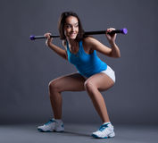 Smiling sporty woman crouches with fitbar Royalty Free Stock Image