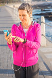 Smiling sporty woman enjoying music and holding phone Royalty Free Stock Photo