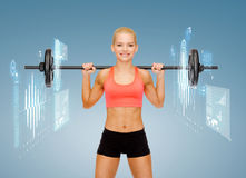 Smiling sporty woman exercising with barbell Stock Photos