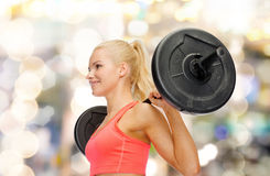 Smiling sporty woman exercising with barbell Stock Image