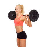 Smiling sporty woman exercising with barbell Royalty Free Stock Photography