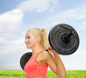 Smiling sporty woman exercising with barbell Stock Photo