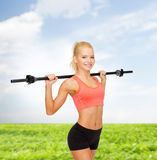 Smiling sporty woman exercising with barbell Stock Images