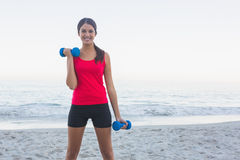 Smiling sporty woman exercising with dumbbells Stock Photo