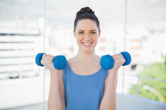 Smiling sporty woman exercising with dumbbells Royalty Free Stock Photos