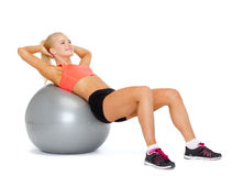 Smiling sporty woman exercising on fitness ball Stock Photo