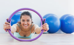 Smiling sporty woman with exercising ring in fitness studio Royalty Free Stock Photo
