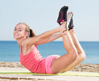 Smiling sporty woman exercising yoga Royalty Free Stock Images