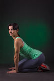 Smiling sporty woman, fitness woman sitting on a dark background with green backlight Stock Images