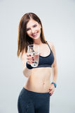 Smiling sporty woman giving glass of water on camera Royalty Free Stock Images