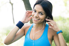 Smiling sporty woman in headphones outdoors Stock Photos
