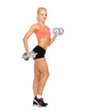 Smiling sporty woman with heavy steel dumbbells Royalty Free Stock Photography