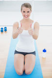 Smiling sporty woman on her knees giving thumbs up to camera Royalty Free Stock Photo