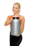 Smiling sporty woman with jar of protein Royalty Free Stock Photo