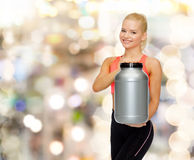 Smiling sporty woman with jar of protein Stock Photo