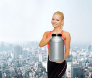 Smiling sporty woman with jar of protein Royalty Free Stock Photography