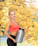 Smiling sporty woman with jar of protein Royalty Free Stock Images