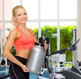 Smiling sporty woman with jar of protein Royalty Free Stock Photos