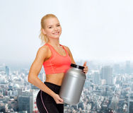 Smiling sporty woman with jar of protein Stock Photography