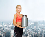 Smiling sporty woman with jar of protein Stock Photos