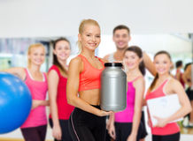 Smiling sporty woman with jar of protein Stock Image
