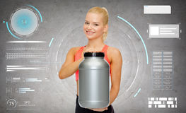 Smiling sporty woman with jar of protein royalty free stock image