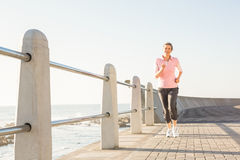 Smiling sporty woman jogging at promenade Royalty Free Stock Photo