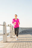 Smiling sporty woman jogging at promenade Stock Photography