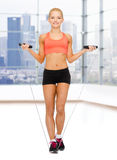 Smiling sporty woman jumping  with skipping rope Royalty Free Stock Image