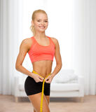 Smiling sporty woman with measuring tape Royalty Free Stock Images