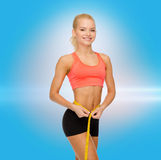 Smiling sporty woman with measuring tape Stock Photo