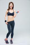 Smiling sporty woman pointing finger away Royalty Free Stock Images