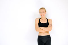Smiling sporty woman portrait with crossed arms against white wa Stock Photography