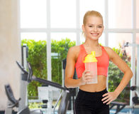 Smiling sporty woman with protein shake bottle Royalty Free Stock Photo