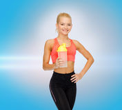 Smiling sporty woman with protein shake bottle Stock Images